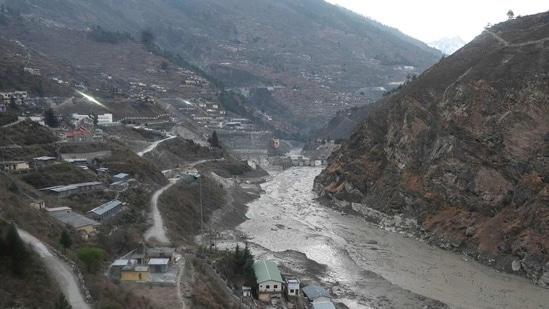 A general view shows the remains of a dam (centre) along a river in Tapovan of Chamoli district(AFP Photo)