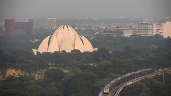 A metro train passes Lotus Temple in the afternoon at Kalkaji in New Delhi.