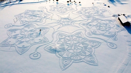A giant complex geometric pattern formed from thousands of footsteps in the snow near to the capital Helsinki, in Espoo, Finland, Sunday Feb. 7, 2021. Under the guidance of an amateur artist Janne Pyykko, 11 snowshoe-clad volunteers stamped a series of complex geometric patterns on a golf course. Together, the designs resemble a huge snowflake. The artwork measures about 160 meters (525 feet) in diameter.(AP)