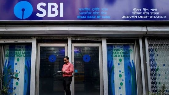A man checks his mobile phones in front of State Bank of India (SBI) branch in Kolkata,.(REUTERS)