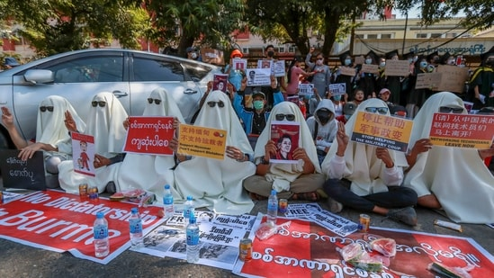 Hooded demonstrators display placards accusing China for supporting Myanmar's military during a protest against the recent coup outside the Chinese Embassy in Yangon, Myanmar, (AP)