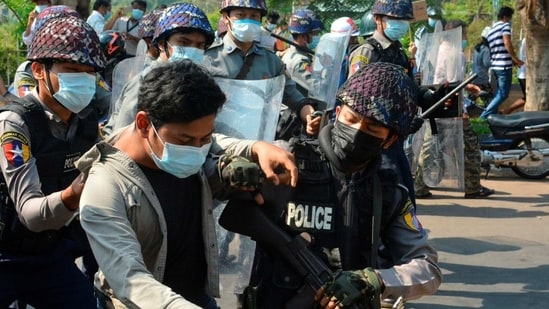 A demonstrator is detained by police officers during a protest against the military coup in Mawlamyine, Myanmar on Friday. ( VIA REUTERS).