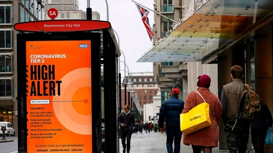 Pedestrians walk past Tier 2 Coronavirus information displayed on an electronic advertising board at a bus stop in central London on December 14, 2020. - The majority of England's 55 million population are under Tier 2 or 3 restrictions, depending on local infection rates. London -- Britain's capital and driving force of the UK economy -- is currently in Tier 2, meaning pubs where food is served and restaurants can open, obeying social distancing rules. But in Tier 3 areas, hospitality venues have to close except for takeaways. (Photo by Tolga Akmen / AFP)(AFP)
