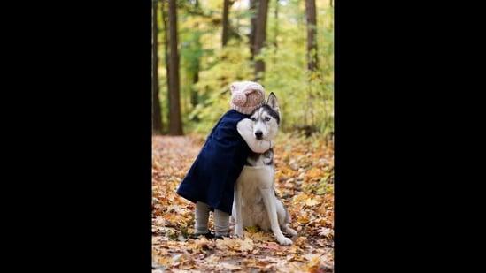 The image shows a kid hugging a dog.(Unsplash)