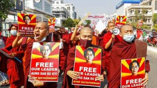 Buddhist monks display pictures of deposed leader Aung San Suu Kyi during a street march against the military coup in Mandalay, Myanmar on Friday, Feb. 12, 2021.(AP)