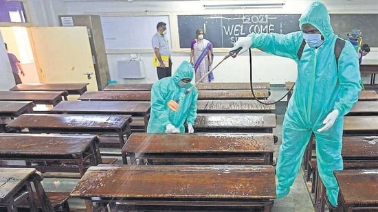 Employees in PPE kits sanitise a classroom at SIES College in Sion, Mumbai. SATISH BATE/HT PHOTO