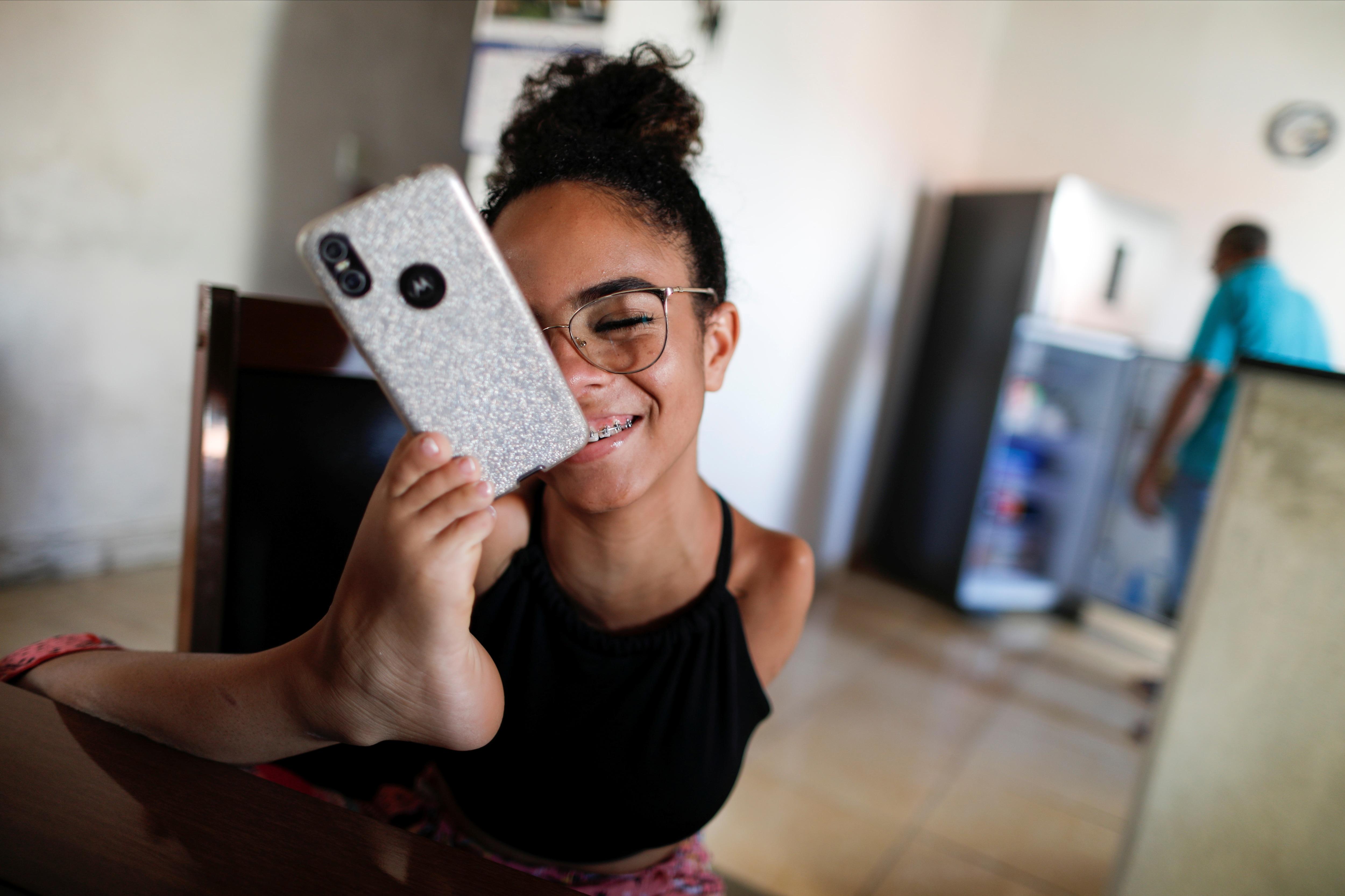 Vitória Bueno conversa com amigas segurando o celular com o pé (REUTERS)