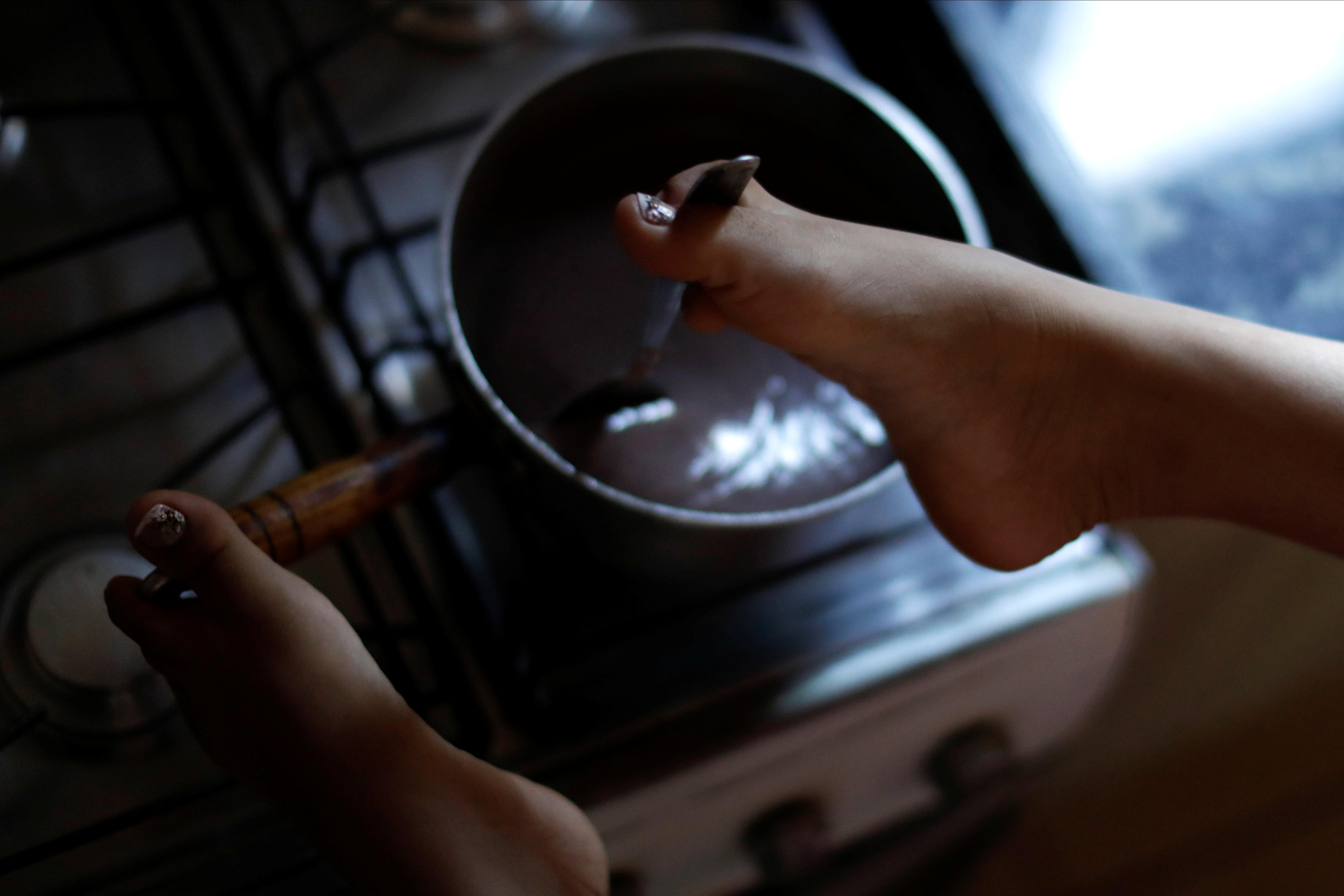 Vitória Bueno usa os pés para cozinhar em sua casa em Santa Rita do Sapucaí, Brasil (REUTERS)