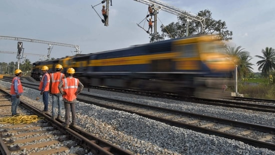 In this representative image, workers on contract for Indian Railways erect infrastructure for drawing electric cable lines over railway tracks for use by locomotives. (AFP)