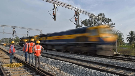 Workers on contract for Indian Railways, erect infrastructure for drawing electric cable lines over railway tracks for use by locomotives on the outskirts of Bangalore on January 15, 2021.(AFP)