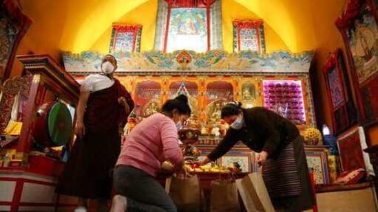 Lama Gelbu, left, Pasang Sherpa, center, and Yanddu Lama, right, prepare bags of fruit used as ceremonial offerings.(AP)