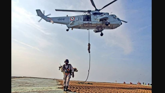 The image shows a Navy diver carrying a sniffer dog.(Twitter/@PRO Defence Mumbai)