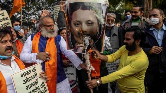 Activists of United Hindu Front (UHF) hold placards and a picture of Swedish climate activist Greta Thunberg during a demonstration in New Delhi on February 4, 2021, after she made comments on social media about mass farmers' protests in India.(AFP)