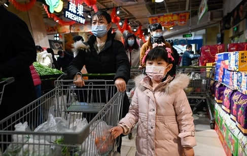 A family pushes a cart with vegetables at a supermarket in Beijing. (AFP)
