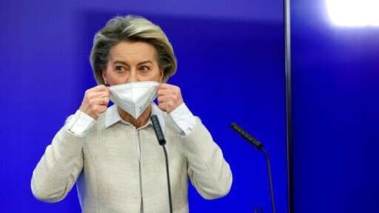 European Commission President Ursula von der Leyen takes off her protective face mask as she prepares to speak during a media conference.(AP)