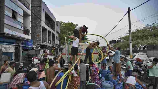 People fill their empty containers with water using lengths of hose pipe from a Delhi Jal Board tanker. (Burhaan Kinu/HT File Photo )