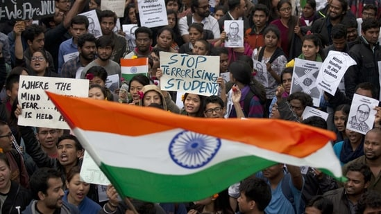 Students wave the national flag and shout slogans during a protest at the Jawaharlal Nehru University against the arrest of a student union leader in New Delhi(AP Photo)