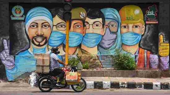 A motorist passes by a mural of frontline workers against coronavirus at RK Puram in New Delhi on July 25. (Sanchit Khanna / HT Photo)