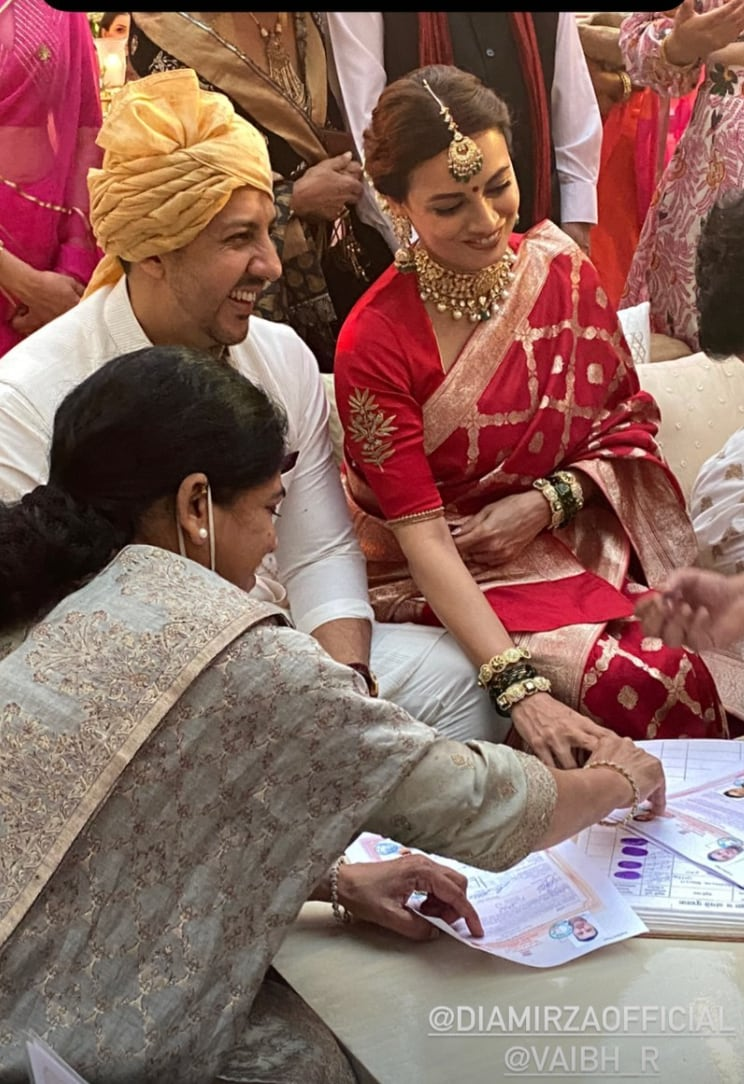 Dia Mirza and Vaibhav Rekhi signing marriage documents.