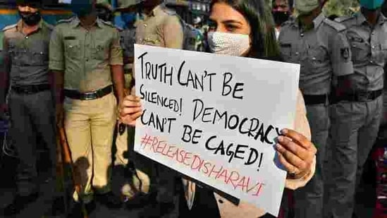 A woman holds a placard next to policemen during a protest against the arrest of climate activist Disha Ravi, in Bengaluru, India.(Reuters)