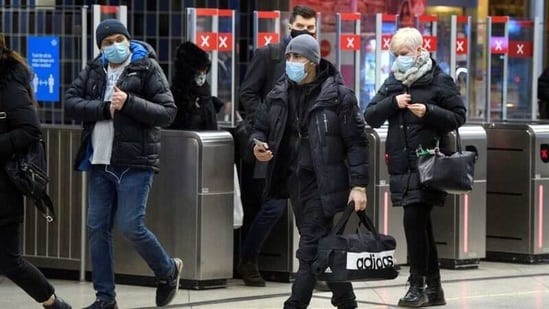 Passengers wearing protective masks enter an underground railway station in Stockholm, Sweden, January 7, 2021.(REUTERS)