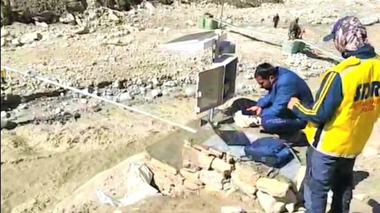 SDRF personnel setting up a siren-based early-warning water level sensor system for a sudden surge in Rishiganga waters in Chamoli district. (HT Photo)