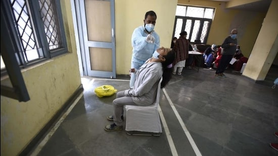 A health worker collects a swab sample from a woman for Covid-19 test in Sector-31, Gurugram. (HT archive)