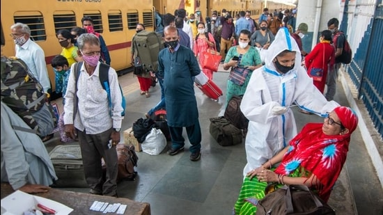 A healthcare worker in PPE kit collects swab samples of a traveller at Dadar station in Mumbai. (Pratik Chorge/HT)