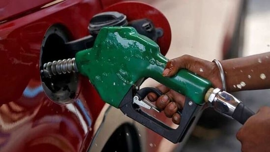A worker holds a nozzle to pump petrol into a vehicle at a fuel station in Mumbai.(Reuters File Photo)