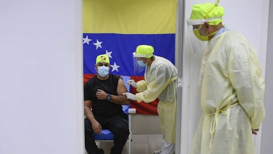 A healthcare worker administers a dose of the Russian Sputnik V Covid-19 vaccine at a health clinic in Caracas, Venezuela.(Bloomberg)