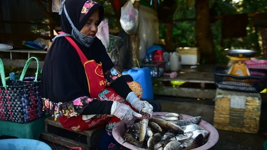 A vendor prepares freshwater fish at a roadside market in southern Thailand's Narathiwat province.(AFP)