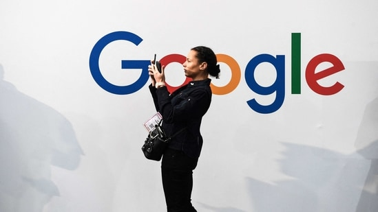 A woman takes a picture with two smartphones in front of the logo of the US multinational technology and Internet-related services company Google.(AP)