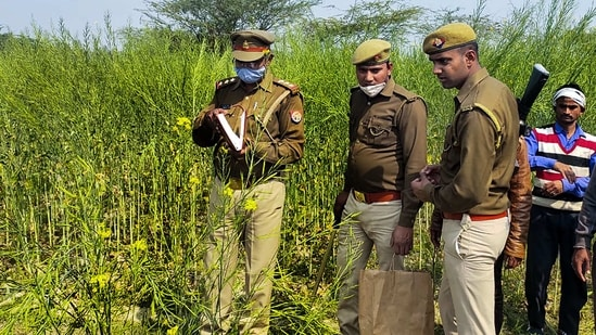Police personnel at the site where bodies of two minor Dalit girls were found in a field on Wednesday evening, in Unnao district.(PTI Photo)