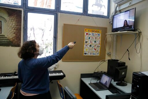 Computer teacher Evi Kontopoulou uses a remote control to find Prospathodas TV, or Trying TV, the channel of Avlonas prison school.(AP)