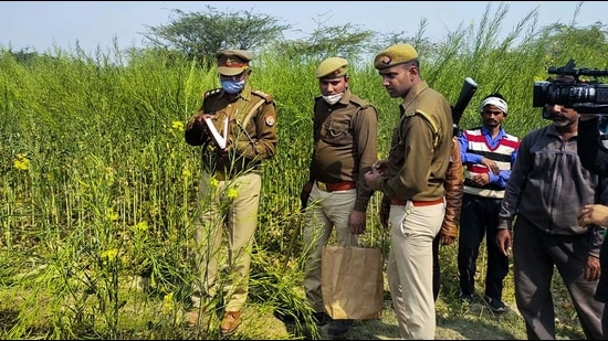 Police personnel investigate at the site where bodies of two minor Dalit girls were found in a field and another in critical condition on Wednesday evening, near Baburaha village in Unnao district, Thursday. (PTI)