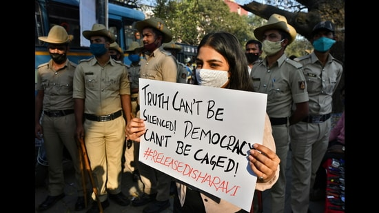 A woman holds a placard next to policemen during a protest against the arrest of climate activist Disha Ravi, Bengaluru, February 15, 2021 (REUTERS)