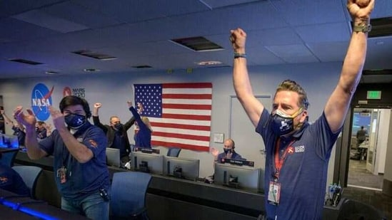 Members of NASA's Perseverance rover team react in mission control after receiving confirmation the spacecraft successfully touched down on Mars.(via REUTERS)