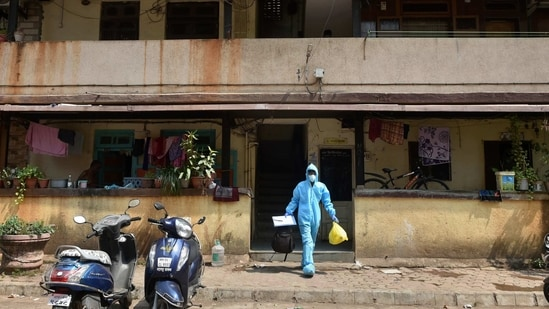 A health worker leaves a residential area after conducting swab tests for Covid-19 following the rise in Corona cases at Dharavi, in Mumbai.(PTI)