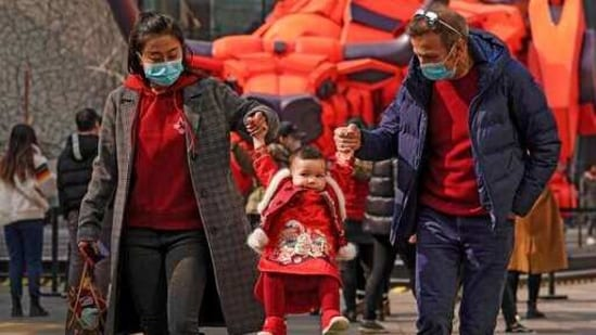 A couple wearing face masks to help curb the spread of the coronavirus lifts their child wearing a new year costume as they visit to the capital city's popular shopping mall during the first day of the Lunar New Year in Beijing, Friday, Feb. 12, 2021. Festivities for the holiday, normally East Asia's busiest tourism season, are muted after China, Vietnam, Taiwan and other governments tightened travel curbs and urged the public to avoid big gatherings following renewed virus outbreaks. (AP Photo/Andy Wong)(AP)