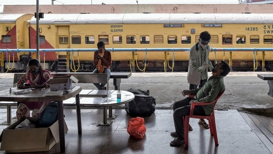 A health worker takes a nasal swab of a passenger for a Covid-19 coronavirus test upon his arrival at the Yeshwanthpur Railway Station, in Bangalore.(AFP)