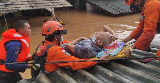 Indonesia's National Search and Rescue Agency shows rescue personnel evacuating an elderly resident from a flooded area in Jakarta.(AFP)
