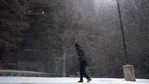 FILE - In this Feb. 14, 2021, file photo, woman walks through falling snow in San Antonio. As temperatures plunged and snow and ice whipped the state, much of Texas' power grid collapsed, followed by its water systems. (AP)