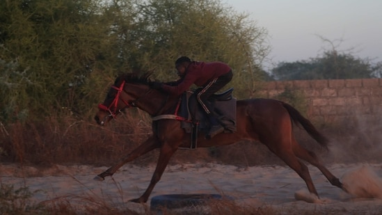 Fallou Diop, 19, a jockey, rides his horse during a training session on a field in Sangalkam, Senegal on January 28.