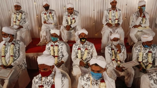 Grooms wearing masks look on during a mass marriage ceremony amidst the spread of the coronavirus disease (Covid-19) in Mumbai, India February 14, 2021. (REUTERS)