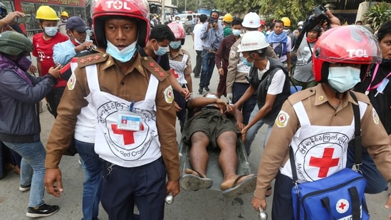 Rescue workers carry an injured man after protests against the military coup, in Mandalay, Myanmar,(Reuters)