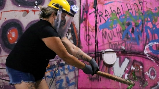 Luciana Holanda smashes a bottle at the Rage Room, a place where people can destroy objects to vent their anger.(REUTERS)