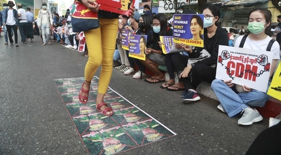Protesters walk over images of military leader during an anti-coup protest outside in Yangon, Myanmar. (AP Photo)