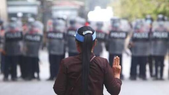 A female protester flashes the three-fingered salute in front of police in Mandalay, Myanmar,(AP)