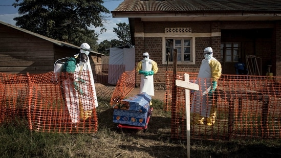Medical workers disinfect the coffin of a deceased unconfirmed Ebola patient inside an Ebola Treatment Centre.(File Photo / AFP)