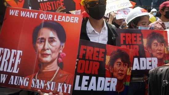 Protesters hold signs calling for the release of detained Myanmar civilian leader Aung San Suu Kyi during a demonstration against the military coup in Yangon on February 21, 2021. (AFP)